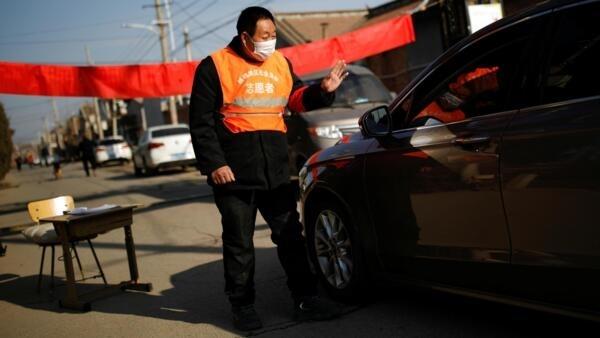 Một người dân ở Điền Gia Doanh (Tianjiayingcun), ngoại ô Bắc Kinh, Trung Quốc, kiểm tra xe hơi vào làng đề phòng dịch virus corona, ngày 29/01/2020