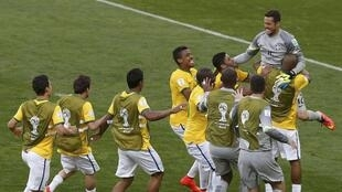 Brazil's goalkeeper Julio Cesar (top R) celebrates with teammates after Chile's Gonzalo Jara (unseen) misses the decisive penalty shot
