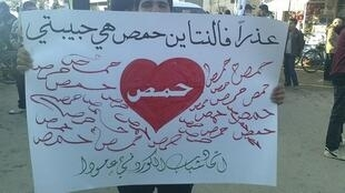 """A man holds a banner that reads """"Sorry Valentine, Homs is my lover"""" in the city of Amude, 14 February, 2012"""