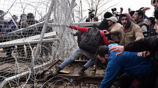 Migrants try to break through a border fence into Macedonia near the Greek village of Idomeni on February 29 , 2016.