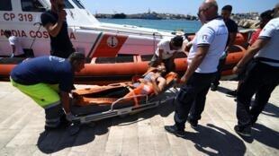 Um migrante que saltou do navio de resgate espanhol Open Arms é transportado numa maca, em Lampedusa, 20 de Agosto de 2019.