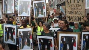 Des militants du climat portent à l'envers les portraits officiels d'Emmanuel Macron volé dans des mairies de France lors d'une marche à Bayonne, près de Biarritz, dans le cadre du sommet du G7, en France, le 25 août 2019.
