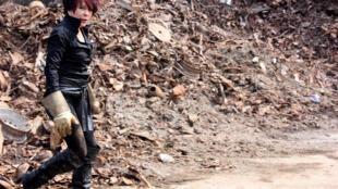Yveline Wood caminha em uma área destruída pela guerra.