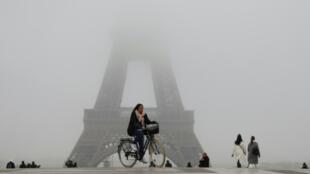 Una mujer circula en bicicleta cerca de la Torre Eiffel de París, cerrada el 5 de diciembre de 2019 por una huelga general en Francia contra la reforma de las pensiones