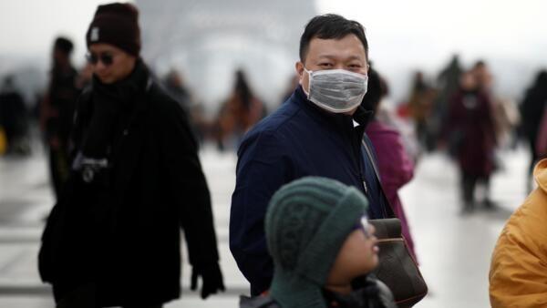 一名佩戴口罩的亞洲男子在巴黎鐵塔前。