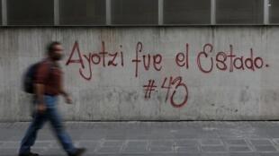 """Na cidade do México, homem passa em frente a um grafite em apoio ao movimento pelos 43 alunos desaparecidos: """"Ayotzy, foi o Estado"""" - 26 de abril de 2015"""