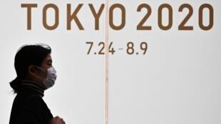 Una mujer protegida con una mascarilla pasa por delante d eun logotipo de los Juegos Olímpicos de Tokio el 24 de marzo de 2020 en la capital japonesa