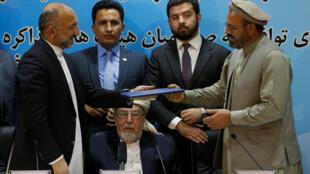Мухаммед Амин Карим (справа), представитель Гульбеддина Хекматияра, и советник по национальной безопасности Афганистана Мухаммед Ханиф Атмар (слева) держат в руках документ после подписания мирного соглашения в Кабуле, 22 сентября 2016.