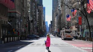 Una mujer atravesando una desolada Quinta Avenida de Nueva York, el 27 de marzo de 2020