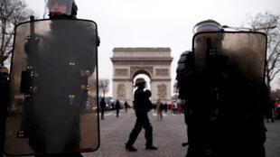 """Oficiais da polícia de choque montam guarda durante uma manifestação pelo movimento """"coletes amarelos"""" na Champs Elysees perto do Arco do Triunfo em Paris, em 29 de dezembro de 2018."""