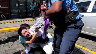 Riot police try to detain a protester in Managua