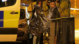 Two women wrapped in thermal blankets near the Manchester Arena after the attack
