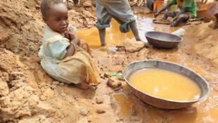 Mina de ouro contaminada por mercúrio (aqui na Tanzânia) onde brinca uma criança junto de garimpeiros.