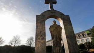 A statue of the late Pope John Paul II is seen under a cross in Ploermel January 25, 2014. Picture taken January 25, 2014.
