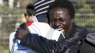 """A migrant hugs a refugee youth service worker as he prepares to take a bus to be transferred to a reception center after the dismantlement of the """"Jungle"""" camp in Calais, France, October 28, 2016."""