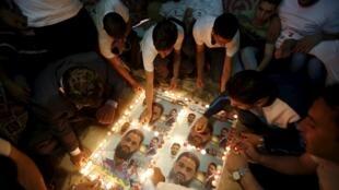 Palestinos de Hebron, na Faixa de Gaza, acendem velas em pôsteres com fotos de Mohammed Allan, detido em Israel, durante protesto, em imagem de 19 de agosto de 2015.