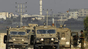 An Israeli soldier stands near armoured jeeps near the border with the northern Gaza Strip