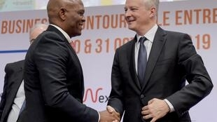 """French Economy and Finance Minister Bruno Le Maire (L) shakes hand with Tony Elumelu, United Bank for Africa president and founder of The Tony Elumelu Foundation, before the opening session of the conference """"Invest for Growth in Africa"""" , October 30, 2019"""