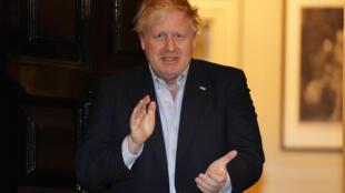 Boris Johnson sale a la puerta del número 10 de Downing Street, su residencia oficial, para aplaudir la labor del personal sanitario en la lucha contra el coronavirus, el 2 de abril de 2020 en Londres