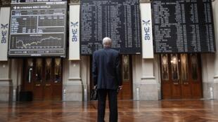 Un corredor observa el panel electrónico de cambios en la bolsa de Madrid.