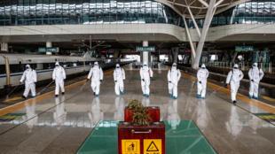 Un grupo de operarios desinfecta los andenes de la estación de trenes de Wuhan, el 24 de marzo de 2020 en la ciudad china