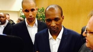Thierry Michel Atangana (C) meets his son Eric (L), who was six at the time of his arrest
