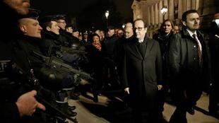 French President Francois Hollande reviews security measures at the Champs Elysees Avenue in Paris on 31 December 2016.