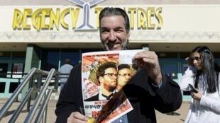 """Dennis Lavalle, do elenco do filme """"The Interview"""", com o cartaz do filme no Regency Theatres, em Los Angeles, no dia 25 de dezembro de 2014."""