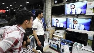 Sanaa residents watch Huthi leader Abdel-Malek al-Houthi on television
