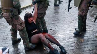 Una manifestante herida es detenida por las fuerzas de seguridad, el 4 de noviembre de 2019 en Santiago de Chile.