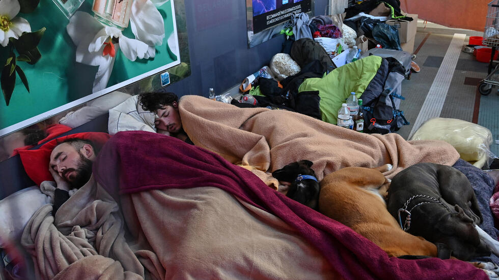 Two men sleep at a homeless camp on March 20, 2020 in a street of Lyon, southeastern France, as a strict lockdown is in effect to prevent the spread of the Covid-19 caused by the novel Coronavirus. The number of people who have died as a result of the coronavirus pandemic now exceeds 10,000, according to an AFP tally based on official data at 1030 GMT Friday.