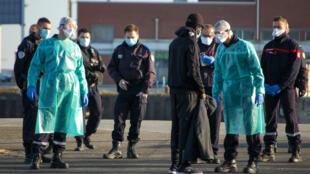 Des gendarmes et des pompiers autour d'un migrant dans le port de Calais, le 7 avril 2020.