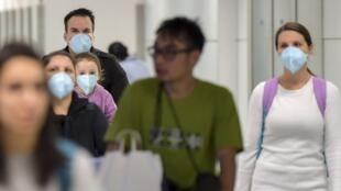 Des passagers portent un masque pour éviter de contracter le virus Covid-19 à l'aéroport international de Guarulhos à Sao Paulo, au Brésil le 26 février 2020.