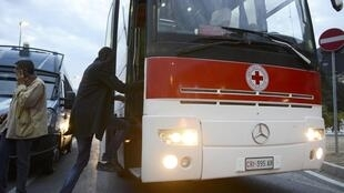 A migrant gets on an Italian Red Cross bus at the Saint Ludovic border crossing between Ventimglia, Italy and Menton, France