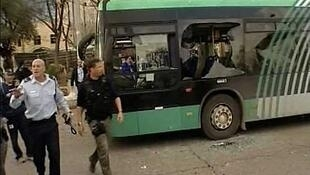 A bus with a damaged window at the scene of the explosion