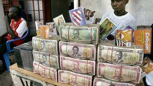 Bundles of Liberian dollars rest on the table of a money changer in Monrovia, 3 October 2005.