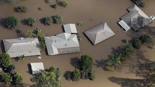 Roofs of houses are visable above flood waters west of Brisbane, 13 January 2011
