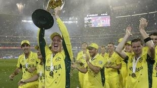 Australia's wicket keeper Brad Haddin holds the Cricket World Cup trophy alongside his team mates, Melbourne Cricket Ground, 29 March 2015.