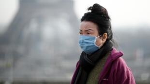 Une femme porte un masque facial sur l'esplanade du Trocadéro en face de la Tour Eiffel à Paris, France, le 25 janvier 2020, alors que la France a confirmé trois cas de nouveau coronavirus.