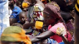 Wasu daga cikin 'yan gudun hijirar da rikicin Boko Haram ya raba da muhallansu, yayin cin abinci a wata cibiyar yi musu rijista a filin wasa na Geidam. 6/5/2015.