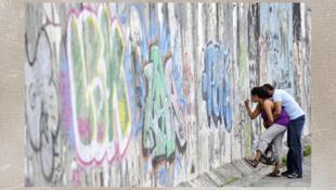 Un couple écrit un message sur les restes du Mur de Berlin.