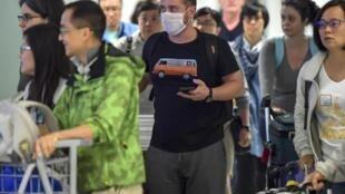 Un passager, portant un masque par mesure de précaution pour éviter de contracter le virus Covid-19, traverse l'aéroport international de Guarulhos, à Guarulhos, Sao Paulo, Brésil le 26 février 2020.