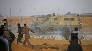 Palestinian protesters hurl rocks at an Israeli army vehicle during a demonstration near the border