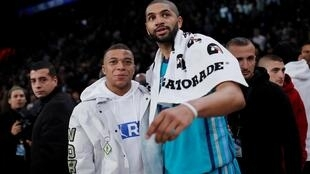 Le basketteur français des Hornets Nicolas Batum pose avec le footballeur Kylian Mbappé lors d'un NBA Paris Game très show.