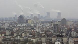 Smoke rises from chimneys on a hazy day in Dezhou, Shandong province, China.