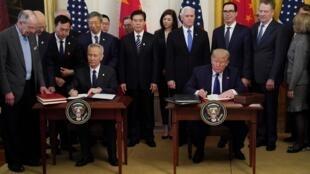中美第一阶段贸易协议15日在白宫正式签署,图为美国总统特朗普与中国副总理刘鹤签署协议。