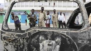 Soldiers and bystanders examine the remains of a car that exploded in Mogadishu on Sunday