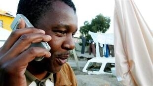 A township resident chats on his mobile phone in Hout Bay near Cape Town
