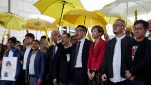 香港占中九子出庭受审前在法院门前,手持象征雨伞运动的黄色雨伞合影。 从左至右依次为:钟耀华,张秀贤,李永达,朱耀明,戴耀庭,陈健民,陈淑莊,邵家臻和黄浩铭。  2018年11月19日