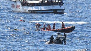 """Em um gesto de desesperto, migrantes transportados pelo """"Open Arms"""" pulam na água antes de serem socorridos pelos guarda-costas italianos."""